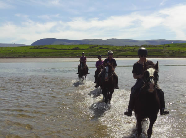 experienced riders riding through sea at Trawalua beach