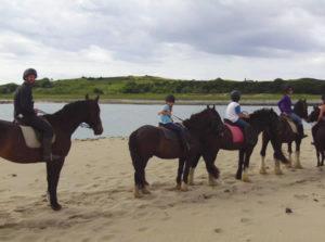 Family riding on Trawalua Beach