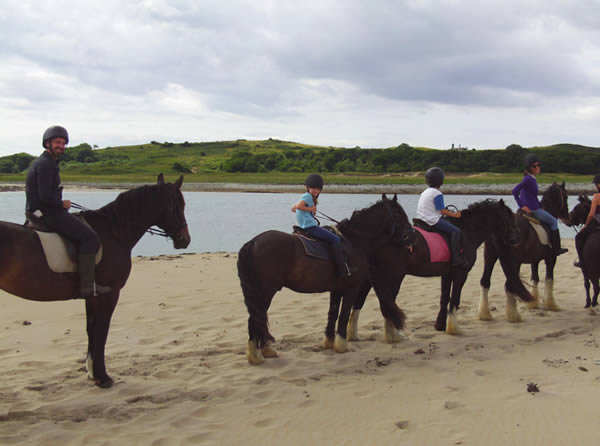 Family riding on Trawalua Beach