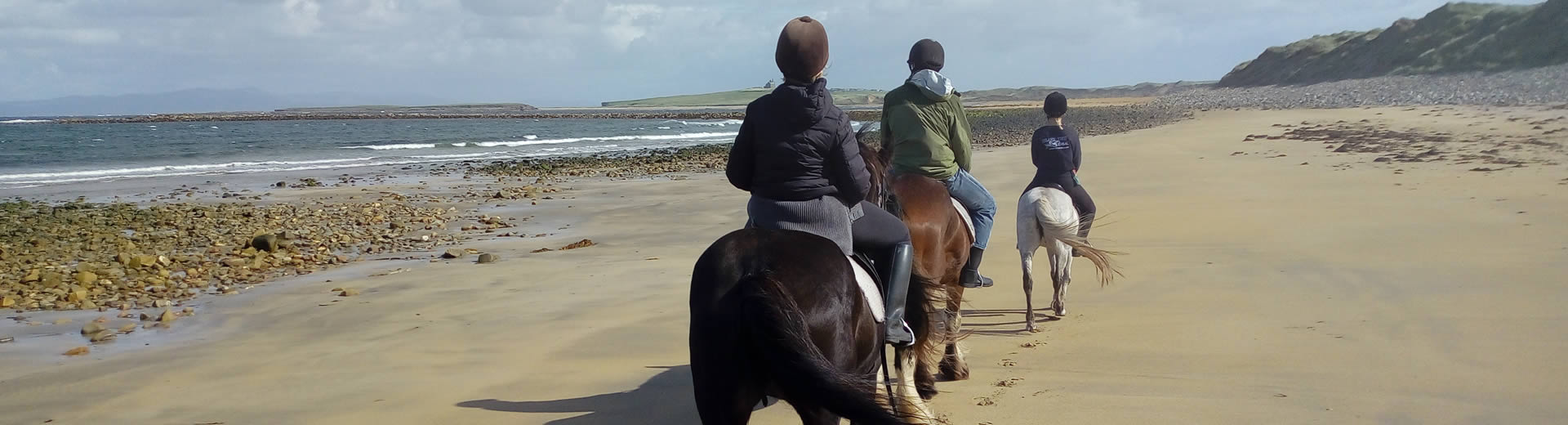 Group out horse riding on a beach in Sligo