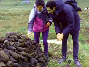 Walkers inspecting stack of turf in Gleniff Valley in Sligo